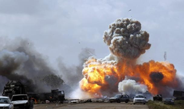 Vehicles belonging to forces loyal to Gaddafi explode after an airstrike by coalition forces along a road between Benghazi and Ajdabiya.