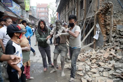 People free a man from the rubble of a destroyed building after an earthquake hit Nepal on April 25th 2015. (Source: EPA/Narendra Shrestha)
